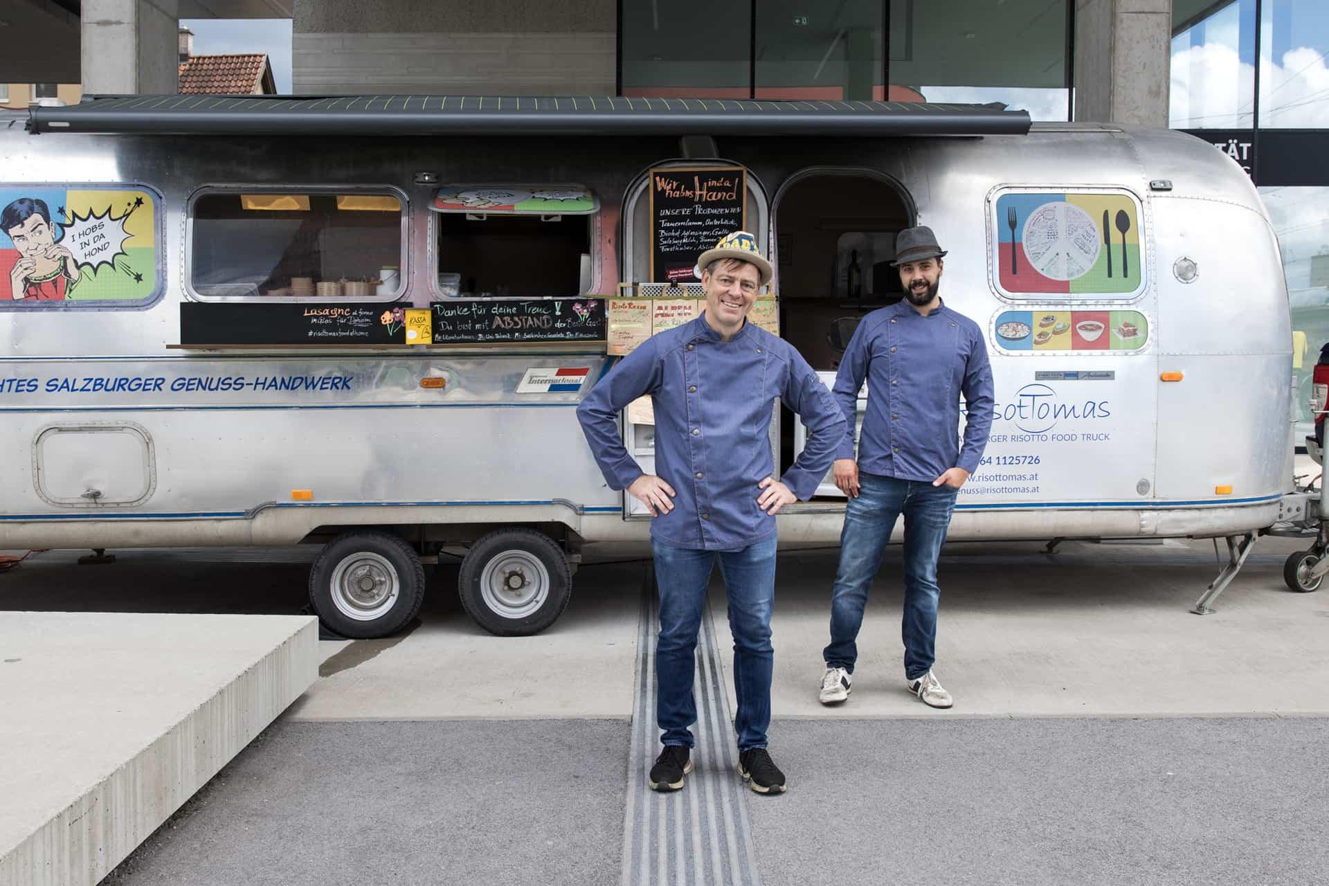 Thomas Enzinger und ein Mitarbeiter stehend vor dem silberfarbigen Foodtruck RisotTomas