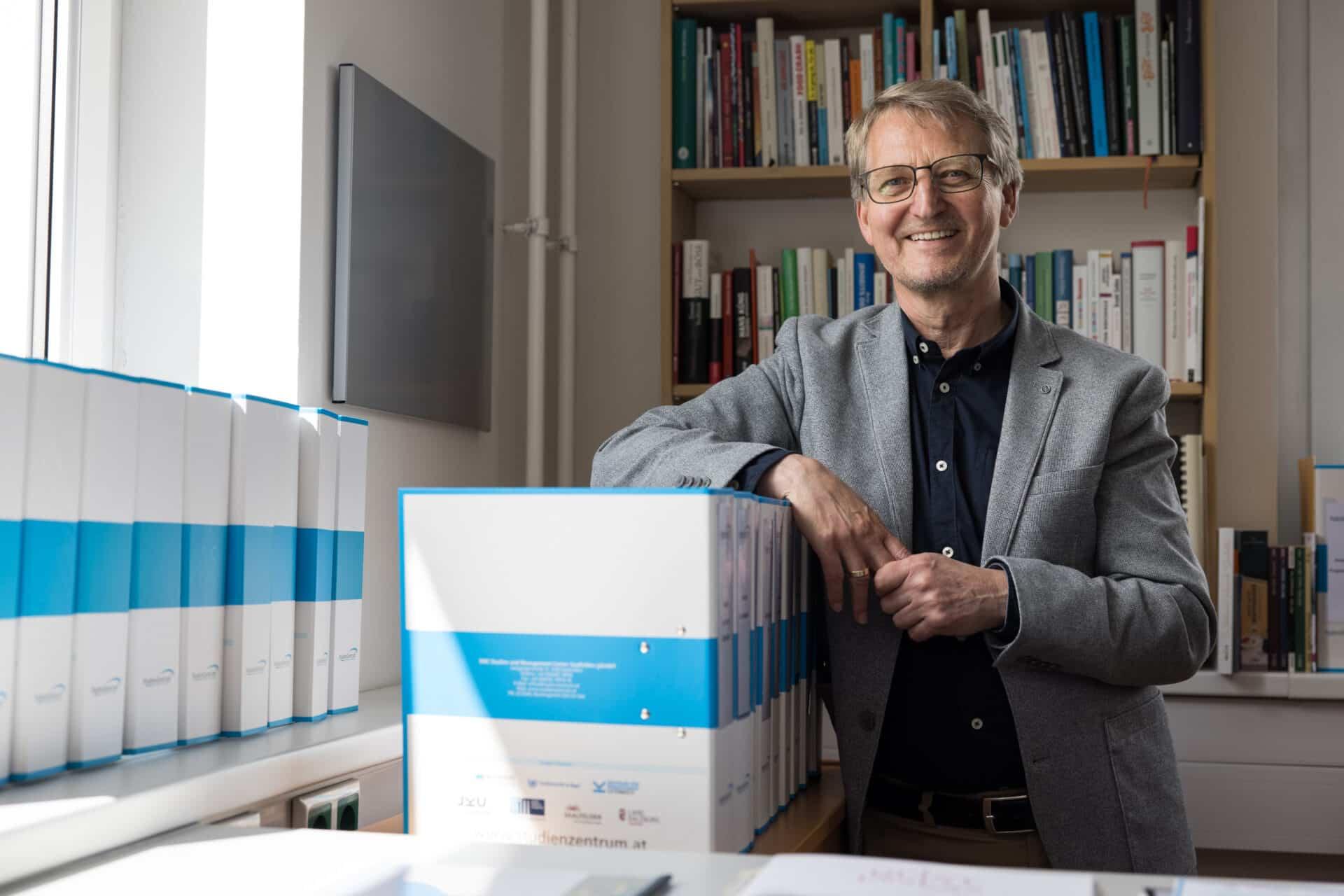 Wolfgang Schäffner stehend im Büro umgeben von Büchern