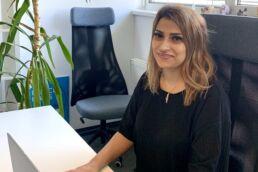 Rasha Fayad sitzend am Schreibtisch vor Computer